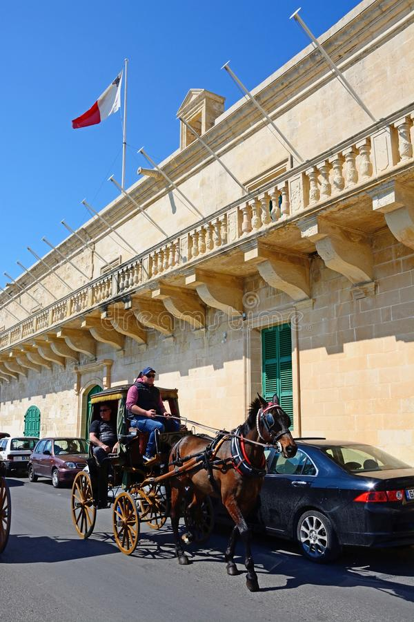 Holy Infirmary, Valletta. Horse drawn carriage passing the Holy Infirmary along Triq Il-Mediterran, Valletta, Malta, Europe royalty free stock images