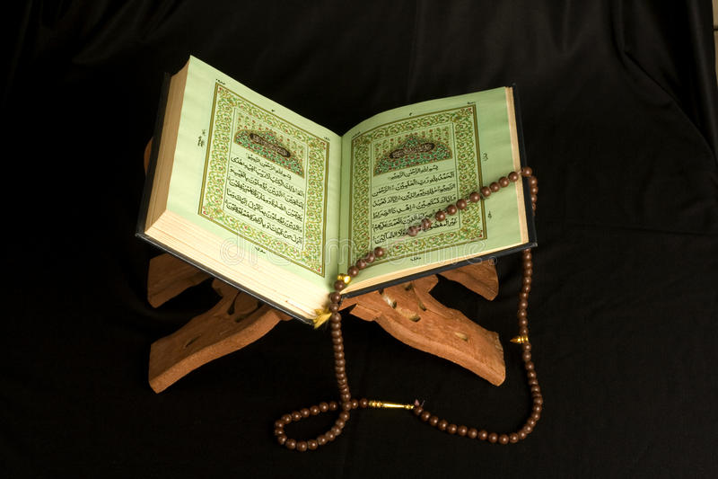 Holy islamic book Koran opened with rosary. On black background royalty free stock photo