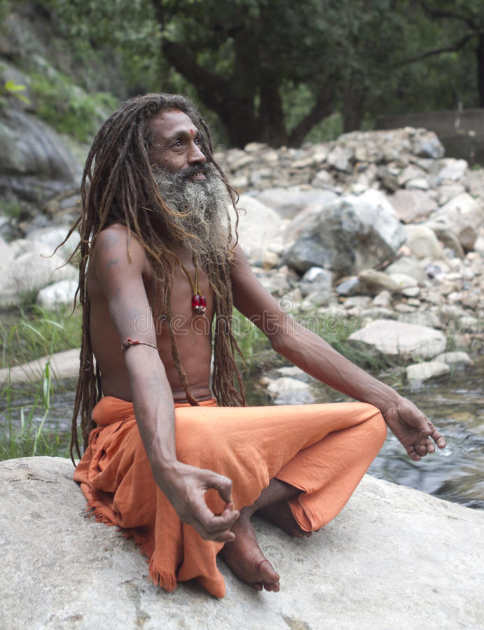 Holy Man. Kathmandu, Nepal - Aug 17, 2012: Sadhu sits at Pashupatinath Temple in Kathmandu, Nepal. Pashupatinath Temple is one of the biggest Hindu temples of royalty free stock image