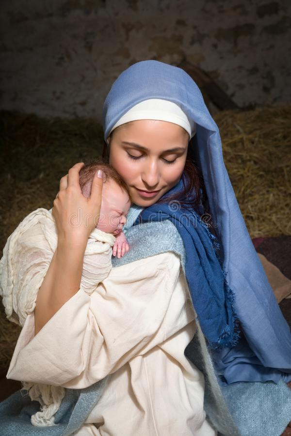 Holy mother with baby Jesus. Live Christmas nativity scene in an old barn - Reenactment play with authentic costumes. The baby is a property released doll royalty free stock images