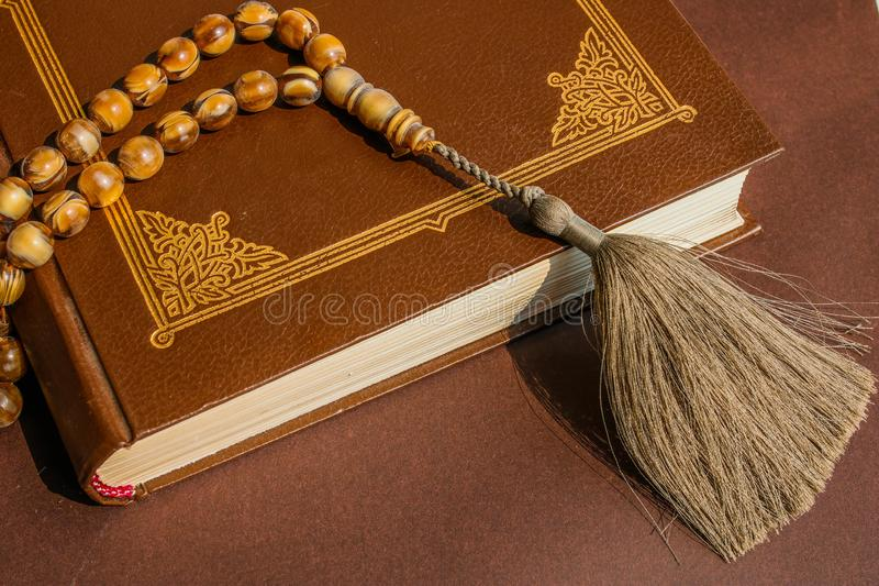 Authentic Islamic rosary on the Holy Quran. Brown Holy book and broun background. Religious concept. Holy Quran with arabic calligraphy and beautiful beads over stock image