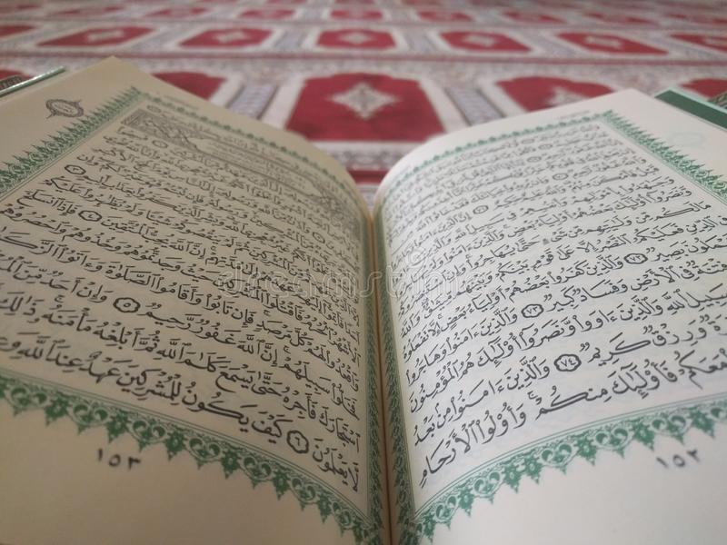 The Holy Quran in English and Arabic on a beautiful Eastern-Pattern Styled Rug. The Holy Quran in English and Arabic is presented on a Quran holder on a royalty free stock images