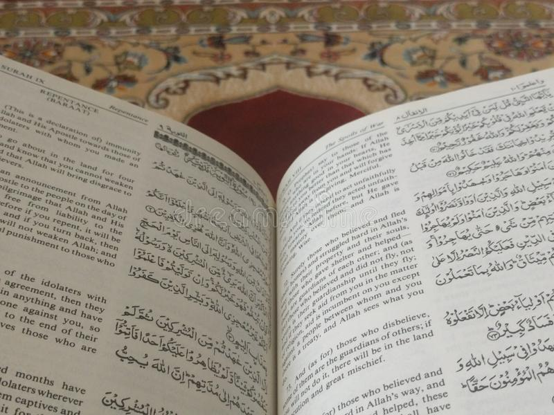 The Holy Quran in English and Arabic on a beautiful Eastern-Pattern Styled Rug. The Holy Quran in English and Arabic is presented on a Quran holder on a stock images