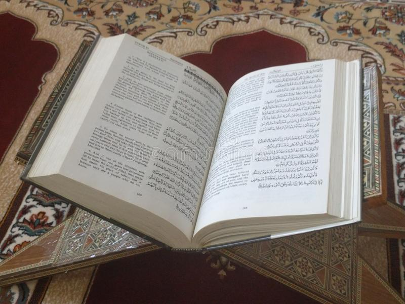 The Holy Quran in English and Arabic on a beautiful Eastern-Pattern Styled Rug. The Holy Quran in English and Arabic is presented on a Quran holder on a stock image