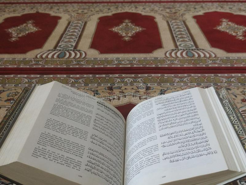 The Holy Quran in English and Arabic on a beautiful Eastern-Pattern Styled Rug. The Holy Quran in English and Arabic is presented on a Quran holder on a royalty free stock photo