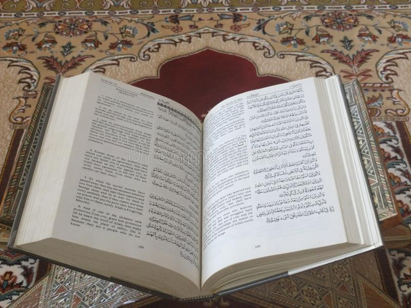The Holy Quran in English and Arabic on a beautiful Eastern-Pattern Styled Rug. The Holy Quran in English and Arabic is presented on a Quran holder on a stock photo
