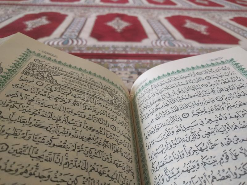 The Holy Quran in English and Arabic on a beautiful Eastern-Pattern Styled Rug. The Holy Quran in English and Arabic is presented on a Quran holder on a royalty free stock photography