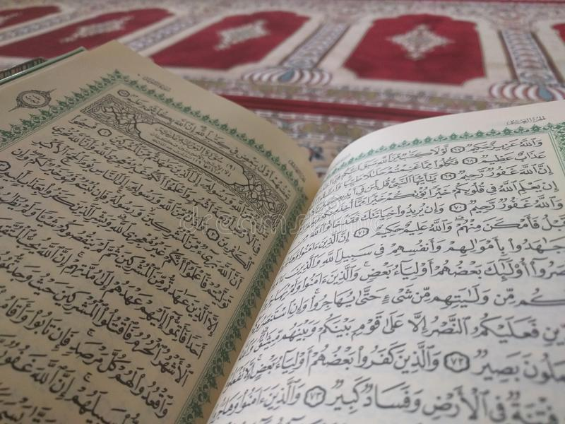 The Holy Quran in English and Arabic on a beautiful Eastern-Pattern Styled Rug. The Holy Quran in English and Arabic is presented on a Quran holder on a stock photos