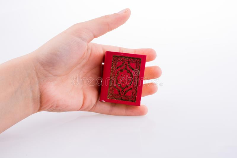 The Holy Quran. Hand holding The Holy Quran on a white background royalty free stock photography