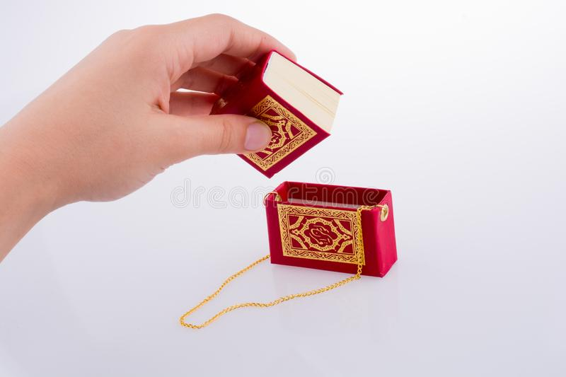 The Holy Quran. Hand holding The Holy Quran on a white background royalty free stock photos