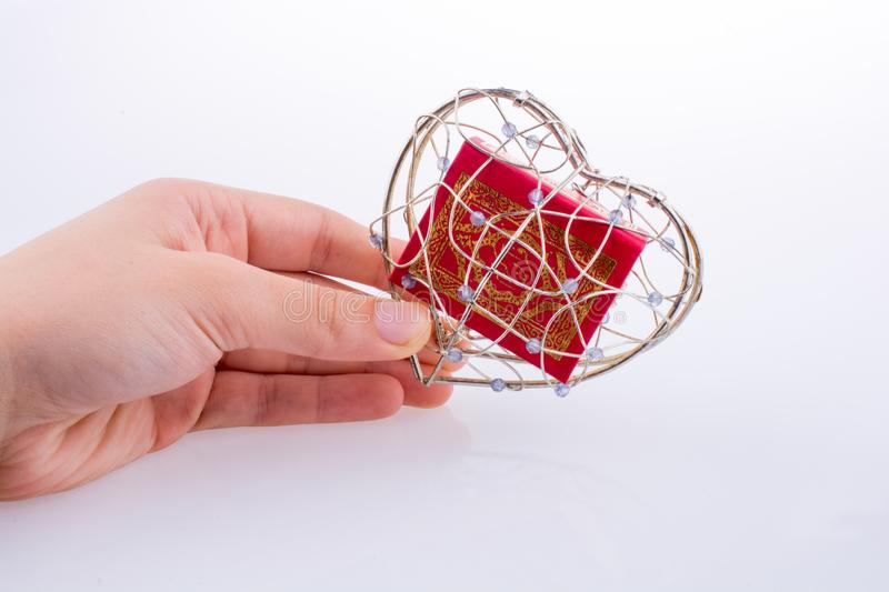 The Holy Quran. In a heart shaped cage on a white background stock image