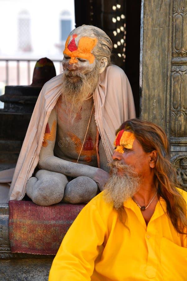 Holy sadhu man in Pashupatinath, Kathmandu, Nepal. KATHMANDU, NEPAL, OCTOBER 8, Holy Sadhu men with dreadlocks and traditional painted face resting at royalty free stock photography