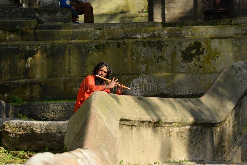 Holy Sadhu man singing on flute in Pashupatinath, Nepal. PASHUPATINATH, NEPAL - OCTOBER 8: Holy Sadhu man singing on flute at Pashupatinath Temple. On October 8 royalty free stock photo