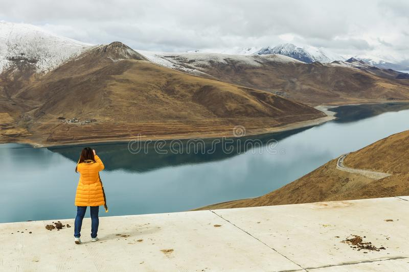 Holy Yamdrok lake and a foreign tourist. Beautiful holy Yamdrok lake with snow mountain in background and a foreign tourist shooting a picture as foreground in a stock photos