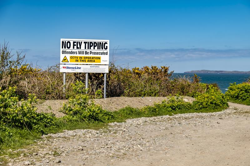 Holyhead , Wales - April 30 2018 : No Tipping warning sign next to the welsh coastline royalty free stock images