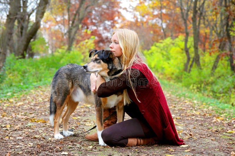 Holz und Schoßhund Womann, die im Holz im Herbst sich entspannen lizenzfreies stockbild