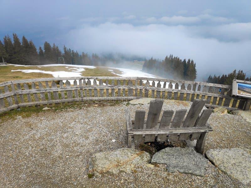Holzbank auf Berg über Wolken stockfotos
