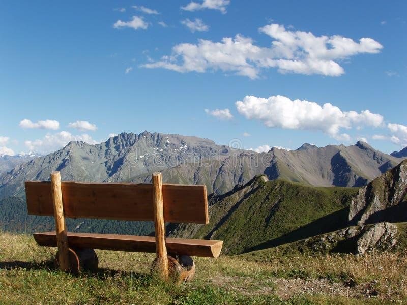 Holzbank mit sch?ner Aussicht von Bergspitzen Silvretta Gruppe, Schweizer Alpen lizenzfreie stockfotos