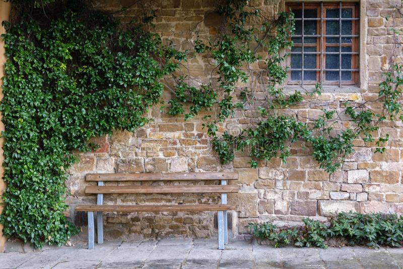 Holzbank neben einer efeubewachsenen Sandsteinwand und einem Eisen-abgehaltenen Fenster stockbild