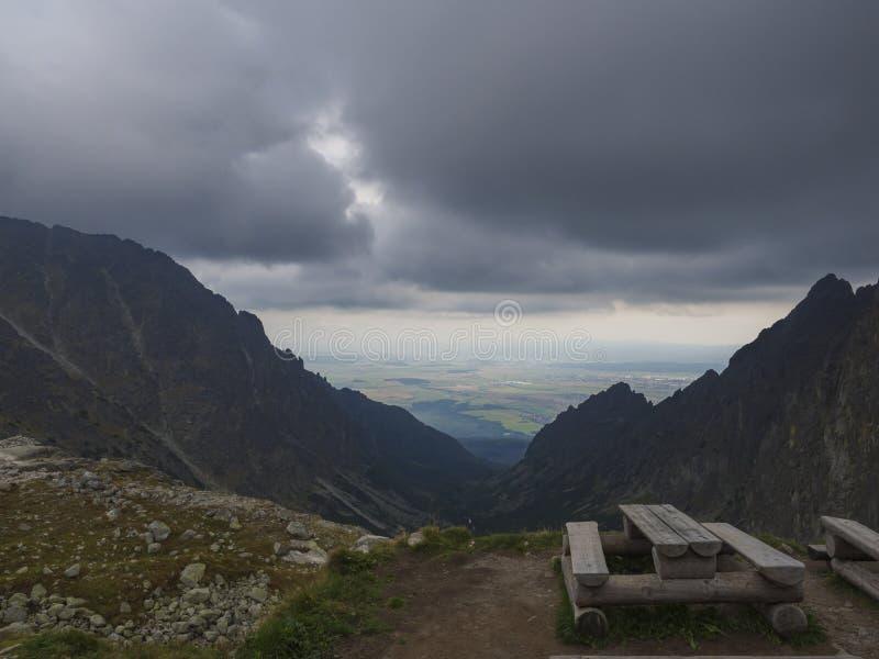 Holzbank und Tabelle für das Essen in den hohen Tatra-Bergen in Slowakei mit Ansicht über Tal und nebeligen Himmel stockfotos