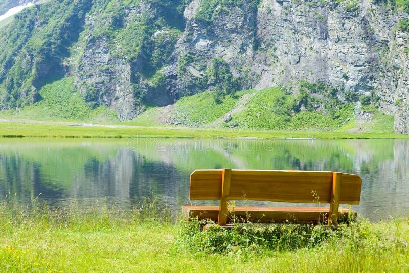 Holzbank vor einem Gebirgssee stockbild
