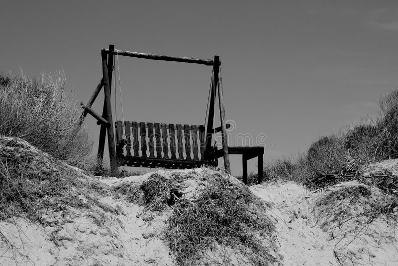 Holzbankschwingen auf verlassener Sanddüne stockfoto