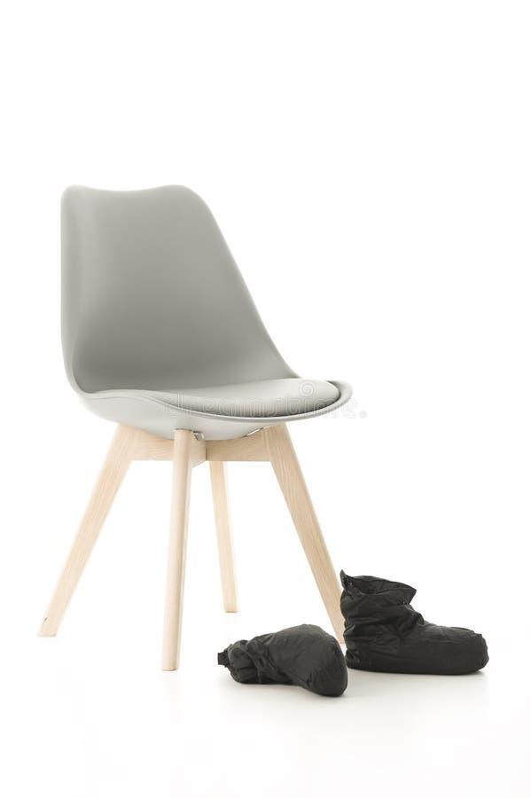 Holzbein-Stuhl und schwarze Stiefel auf Weiß lizenzfreie stockfotografie