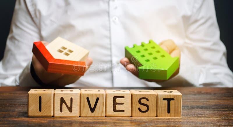 Holzblöcke mit dem Wort Invest und Häuser in den Händen eines Geschäftsmannes Das Konzept der Investition in den Immobilienbau lizenzfreies stockfoto
