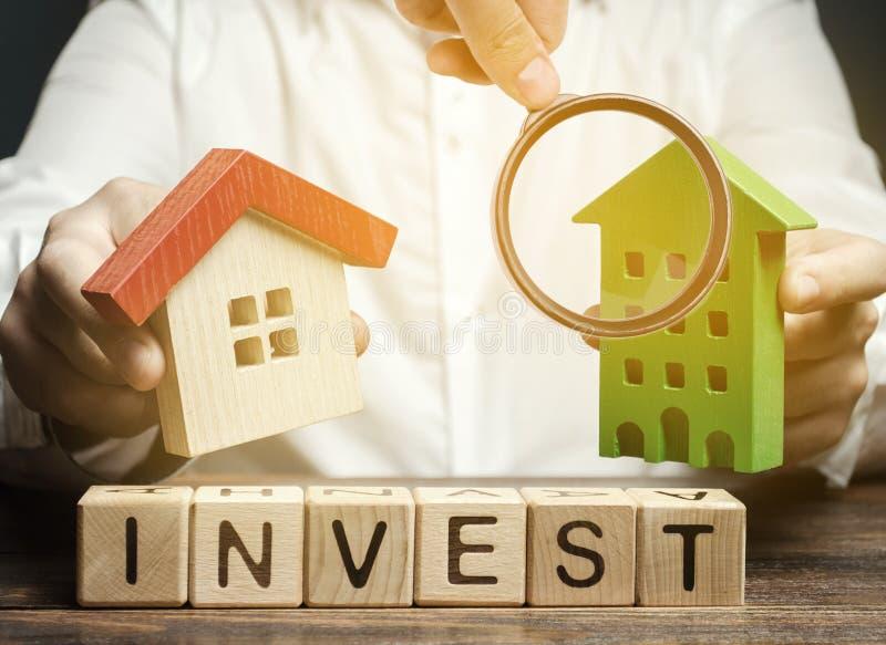 Holzblöcke mit dem Wort Invest und Häuser in den Händen eines Geschäftsmannes Das Konzept der Investition in den Immobilienbau stockfotografie