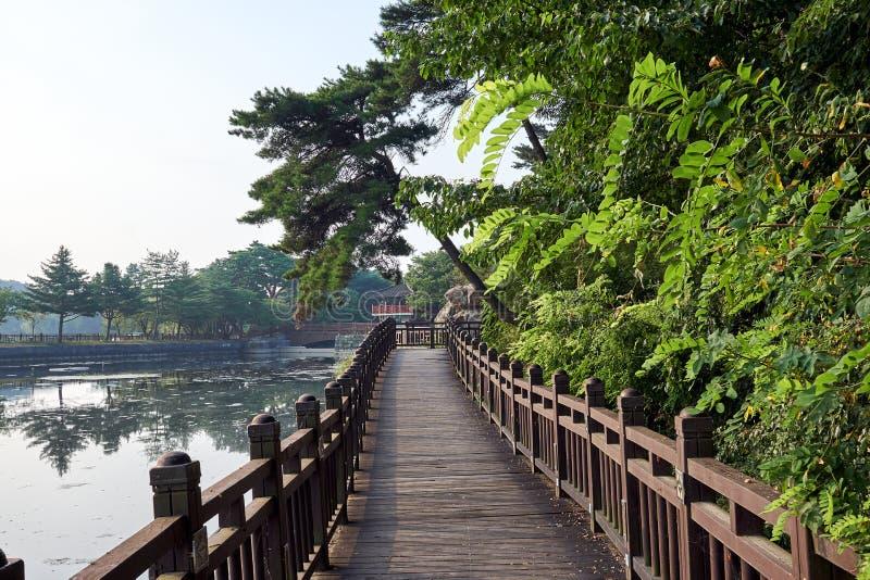 Holzbrücke über dem Uirimji-Reservoir, das zu einen Gazebo übersieht den See in Jechun, Südkorea führt lizenzfreie stockfotos