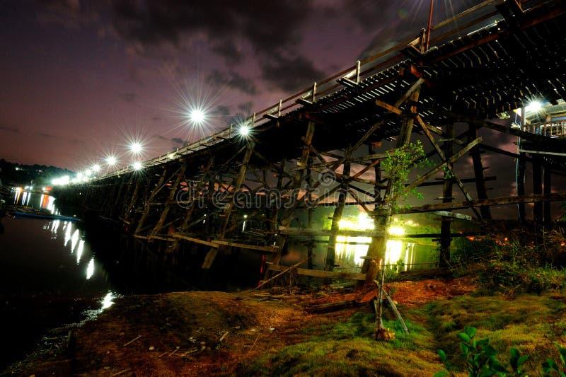 Holzbrücke über Flusssonnendämmerung lizenzfreies stockbild