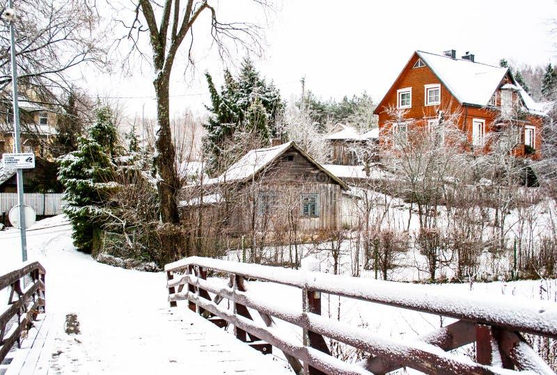 Holzbrücke im Winter, in den Bäumen und und in den Holzhäusern bedeckt durch Schnee stockfotografie