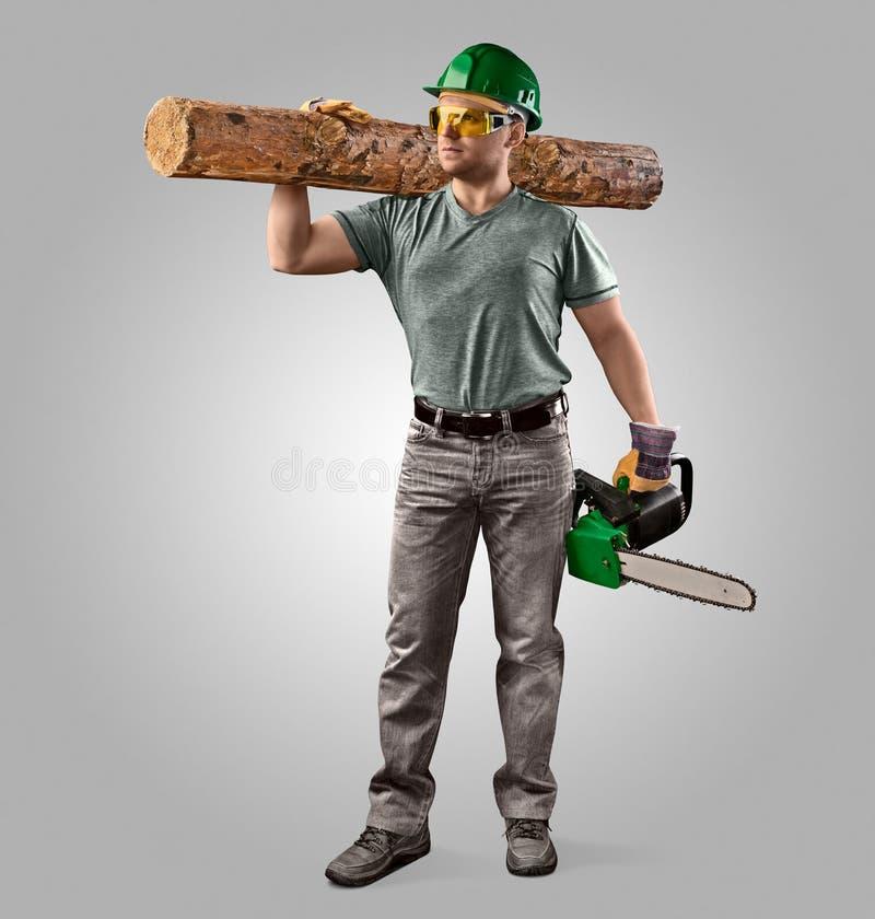 Holzfäller im Sturzhelm mit Kettensäge und Klotz lizenzfreies stockfoto
