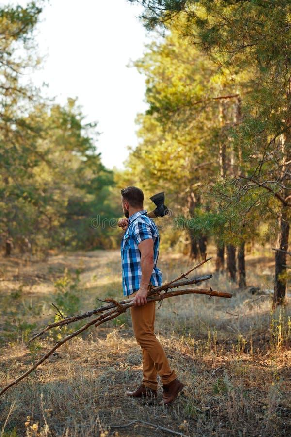 Holzfäller mit Axt und Brennholz läuft Wald durch stockfotografie