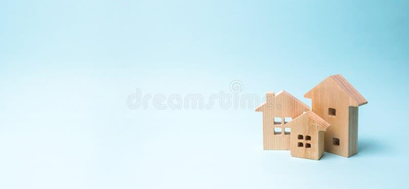 Holzhäuser auf einem blauen Hintergrund Hölzerne Spielwaren Das Konzept von Immobilien und Besitz, Kauf des Eigentums Bauernhof,  lizenzfreies stockfoto