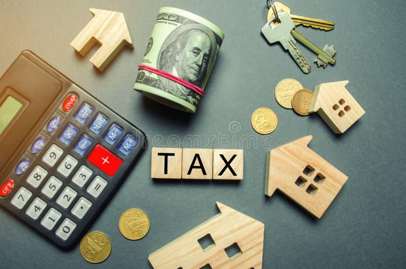Holzhäuser, ein Taschenrechner, Schlüssel, Münzen und Blöcke mit der Wort Steuer Vermögenssteuern Berechnung von Zinsen auf Hauss lizenzfreies stockfoto