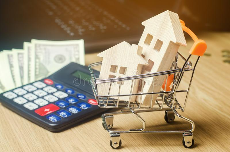 Holzhäuser in einer Supermarktlaufkatze, im Geld und in einem Taschenrechner Real Estate-Markt Analytics Grundbesitzkonzept 6 Ver stockbild