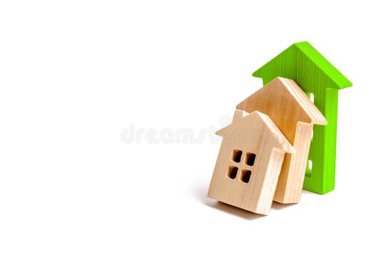 Holzhäuser fallen auf einander wie Dominos das grüne Haus stoppt den Fall anderer Häuser Das Konzept von fallenden Preisen stockbild