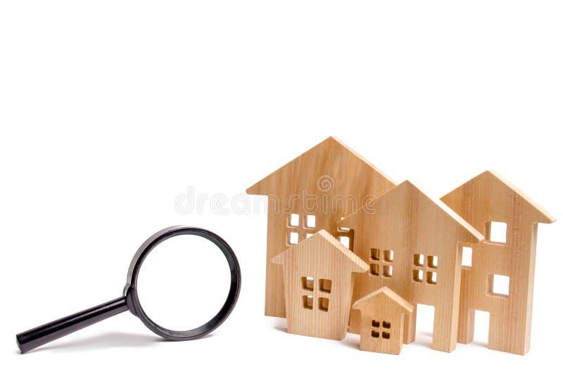 Holzhäuser und Lupe auf einem weißen lokalisierten Hintergrund Hauptsuchkonzept Erschwingliches Gehäuse Mietwohnung oder stockbild