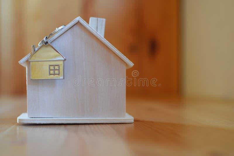 Holzhaus mit Schlüsselring und Anhänger in Form des Hauses lizenzfreies stockbild