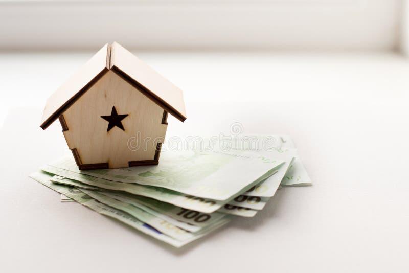Holzhaus steht auf einem Stapel von den Papierrechnungen, die als Symbol der Hypothek Euro sind lizenzfreies stockbild
