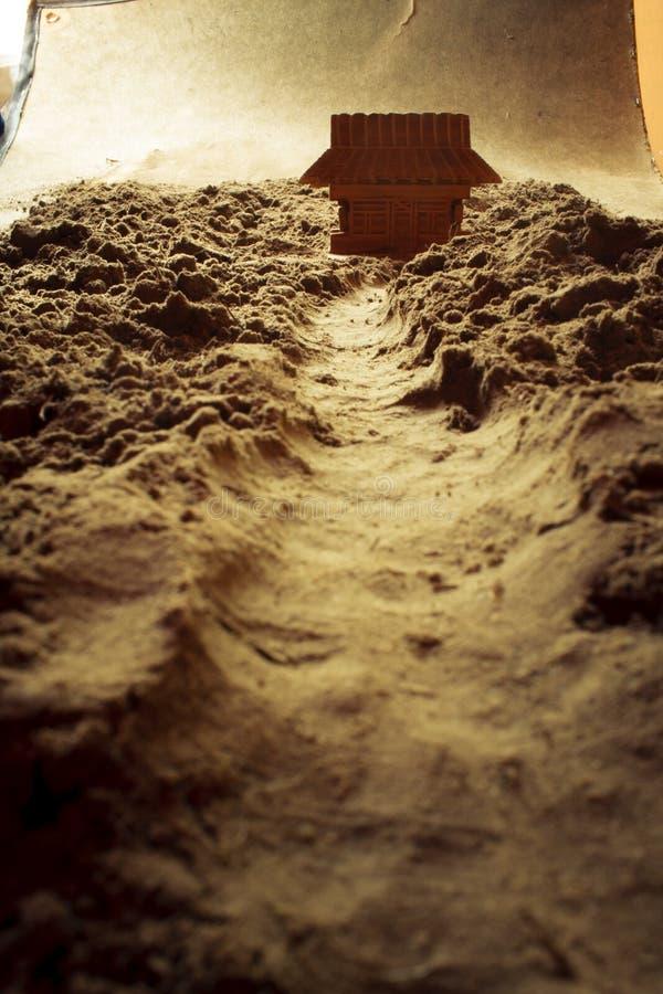 Holzhaus und ein Baum in einer Wüste - Makrozusammensetzung flach lizenzfreies stockfoto