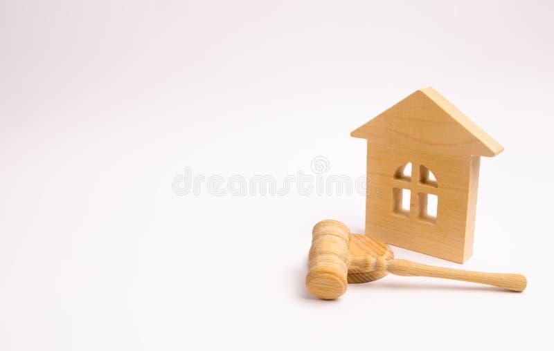 Holzhaus und Hammer des Richters auf einem weißen Hintergrund Konzeptversuchseigentum Das Gerichtsurteil auf der Eigentumsübertra stockfoto