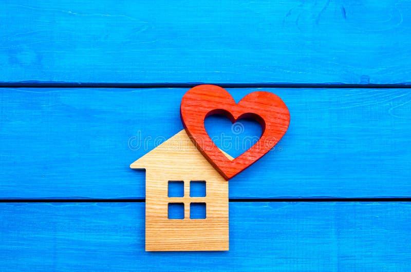 Holzhaus und rotes Herz auf einem blauen hölzernen Hintergrund stockfoto