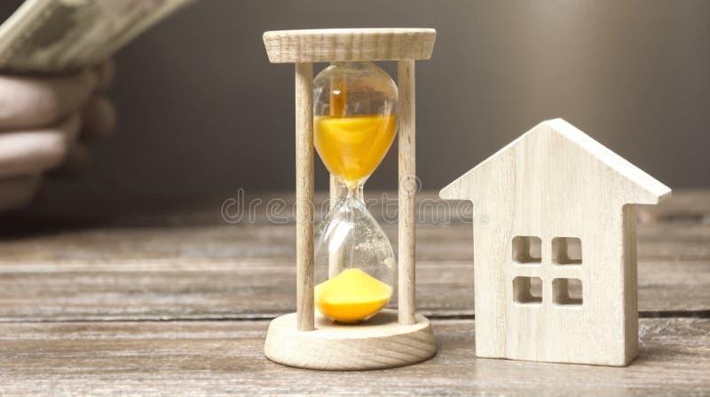 Holzhaus und Uhr Gesch?ftsmann, der Geld z?hlt Zahlung der Ablagerung oder Vorauszahlung f?r das Mieten eines Hauses oder der Woh lizenzfreie stockfotos
