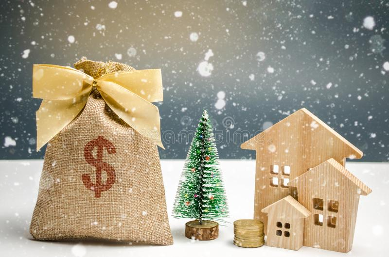 Holzhaus- und Weihnachtsbaum und eine Tasche des Geldes Weihnachtsverkauf von Real Estate Rabatte des neuen Jahres für kaufendes  stockfoto