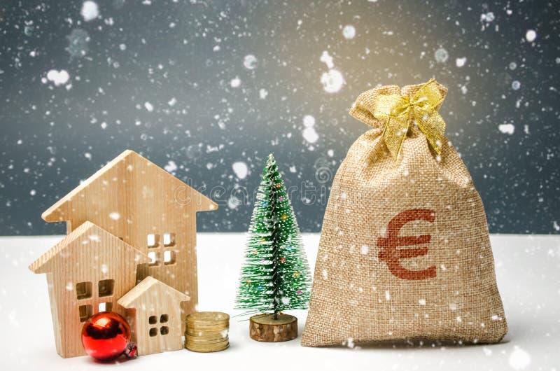 Holzhaus- und Weihnachtsbaum und eine Tasche des Geldes Weihnachtsverkauf von Real Estate Rabatte des neuen Jahres für kaufendes  lizenzfreie stockfotos