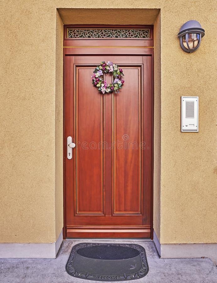 Holzhaustür mit zuerst des Mai-Blumenkranzes lizenzfreies stockbild