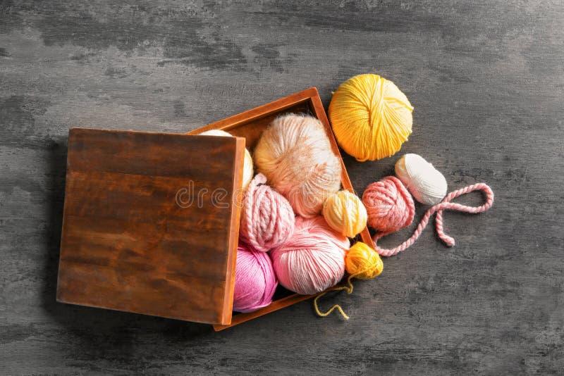 Holzkiste mit buntem Strickgarn auf Tabelle stockfoto