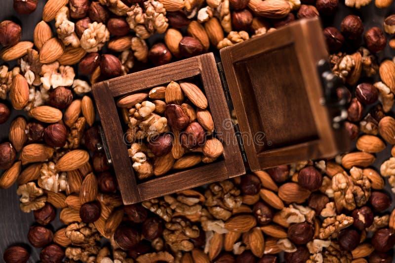 Holzkiste voll Nüsse und Nüsse zerstreute herum, Haselnüsse, Walnüsse und Mandeln stockfotografie